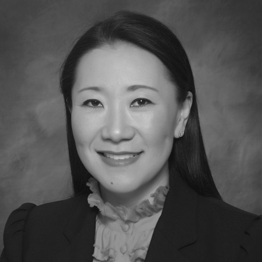 Black and white portrait image of an Asian woman Jinny Lee smiling for photograph.