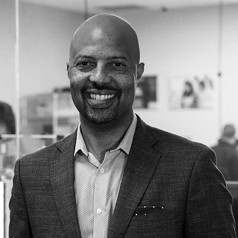 Black & White photo of African American Man smiling. He is wearing a dotted dress shirt with a black suit.