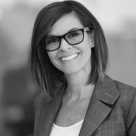 Black & White photo of dark haired Caucasian Woman smiling. She is wearing glasses.