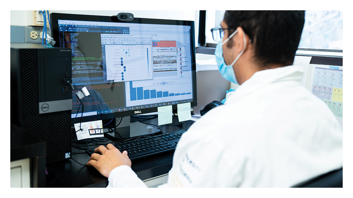 A man wearing a mask and white lab coat works on a computer with graphs