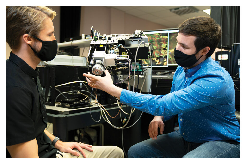 Two men sit in a lab and examine optical equipment