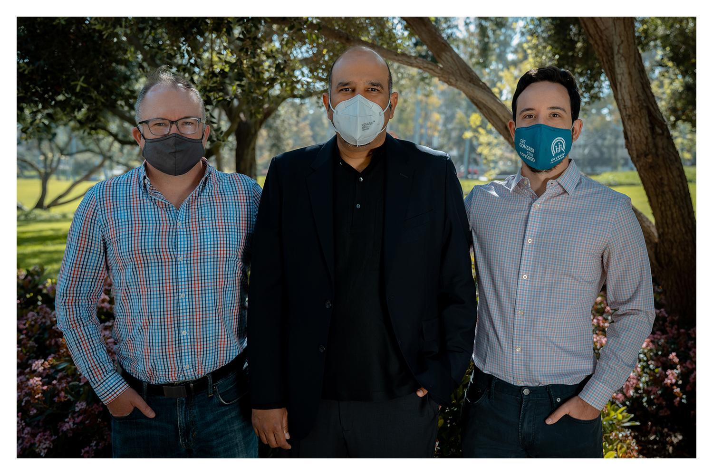Three men in masks standing outside