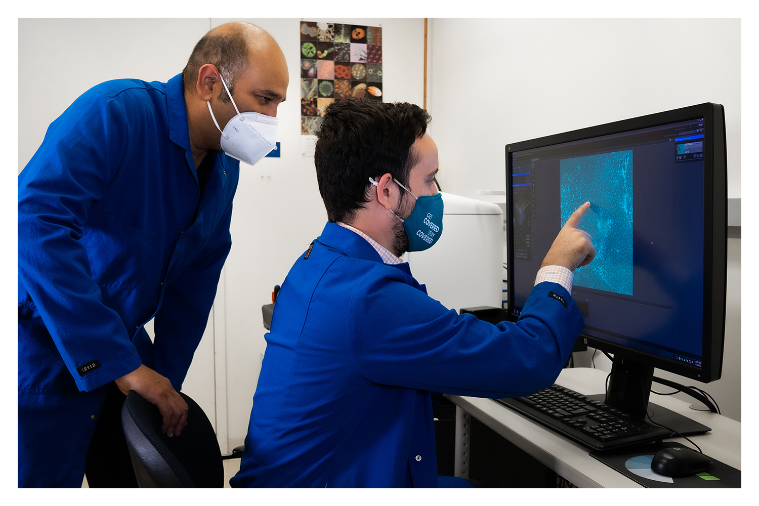 Two men inspect images on a computer screen