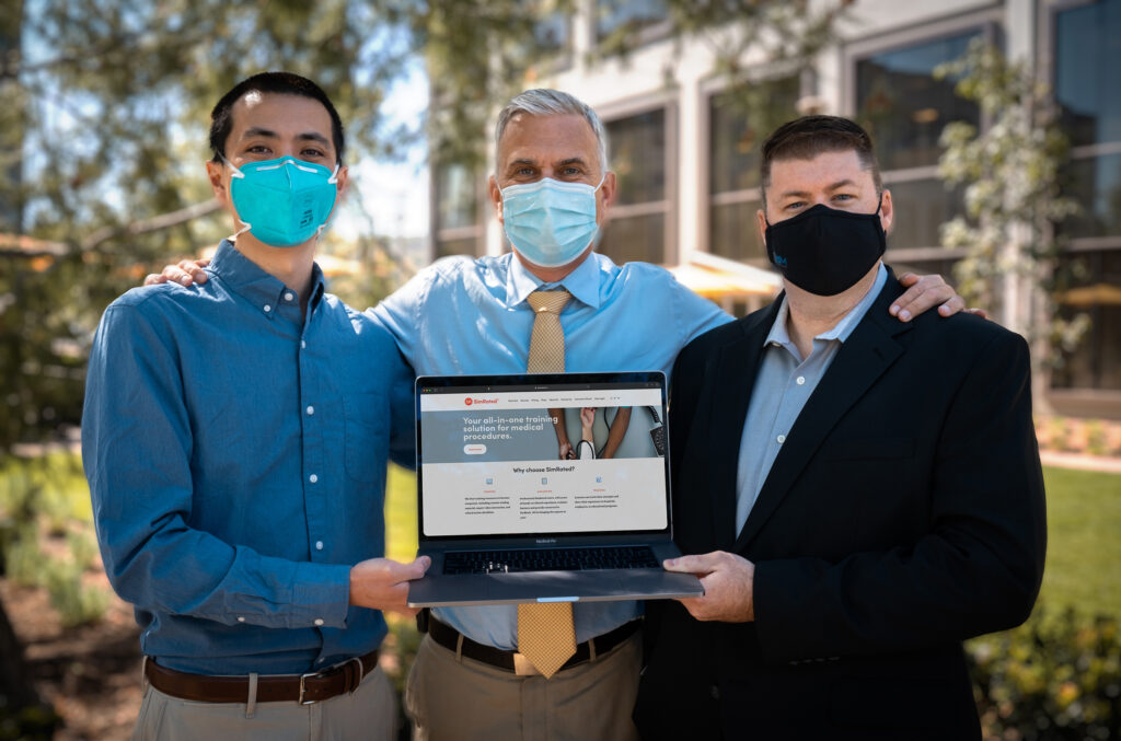 three men wearing face masks stand together and hold a laptop displaying their online medical education program
