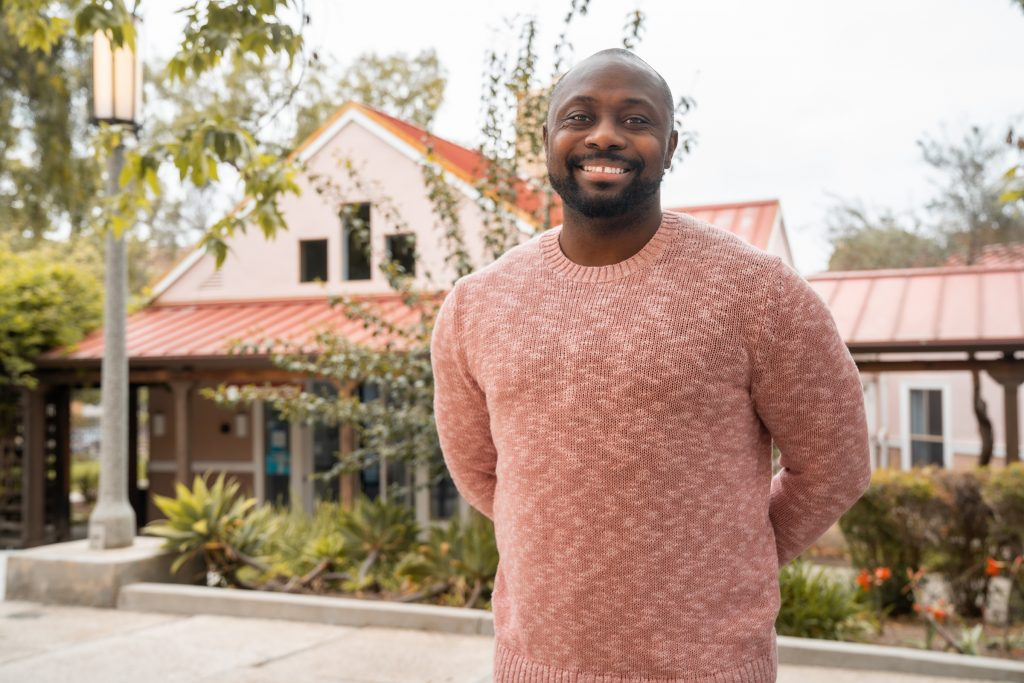black man in a red sweater smiles while standing in front of a building holding his hands behind his back