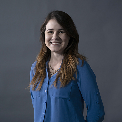 Photograph of a smiling Caucasian woman in a blue blouse posing for photograph