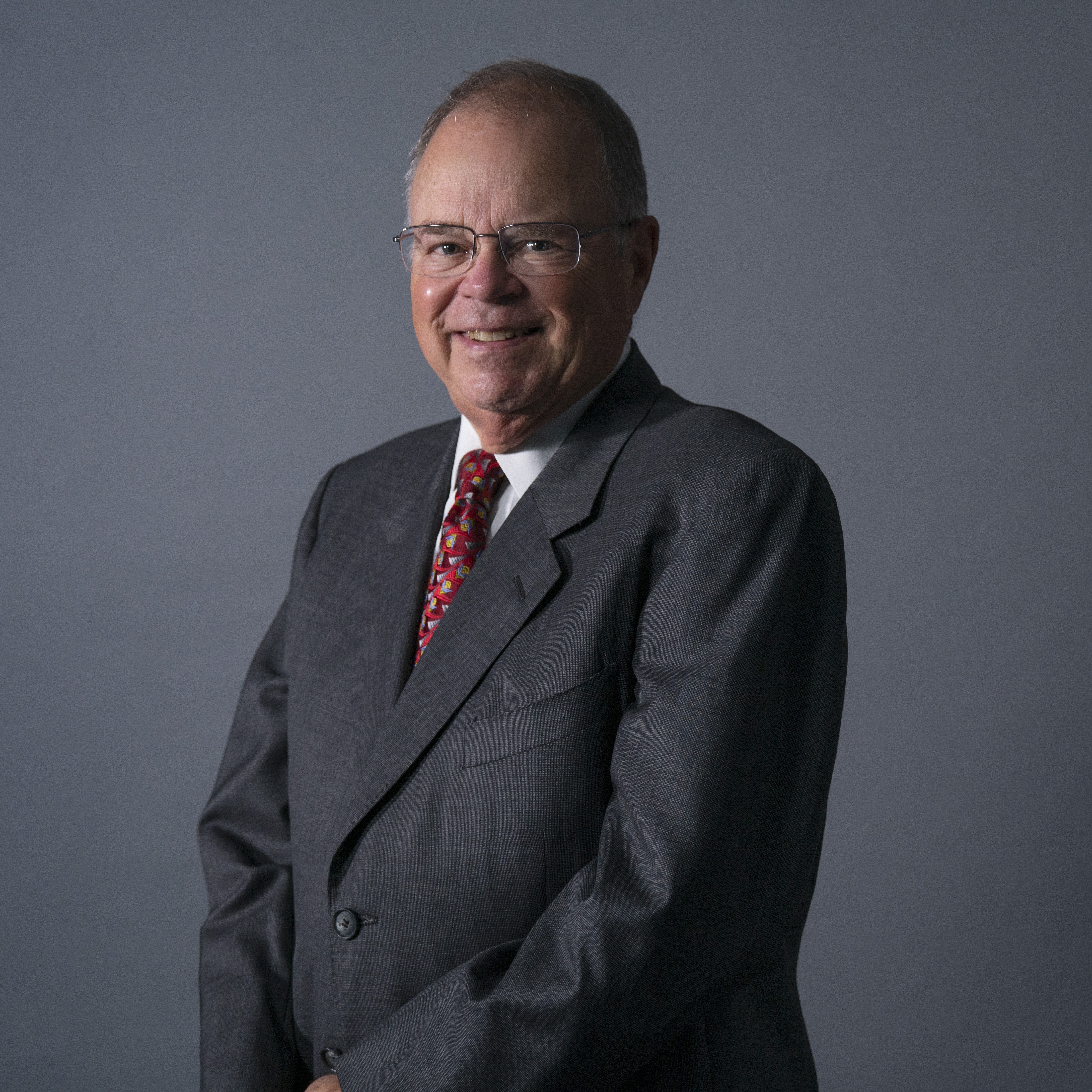 Photograph of Caucaisan man with glasses, wearing a grey suit with a red printed tie.