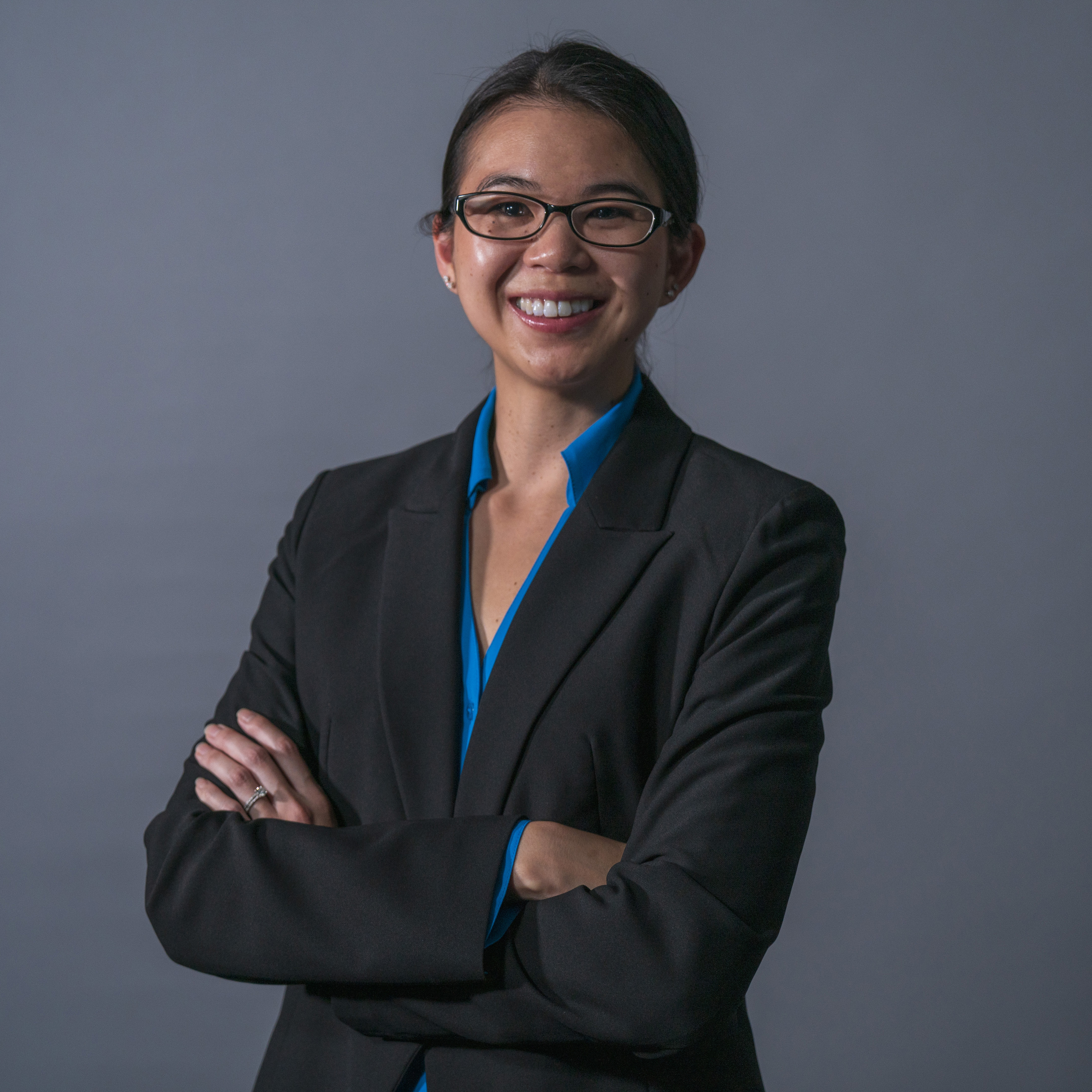 Photograph of smiling Asian woman wearing black framed glasses, black suit posing for camera.