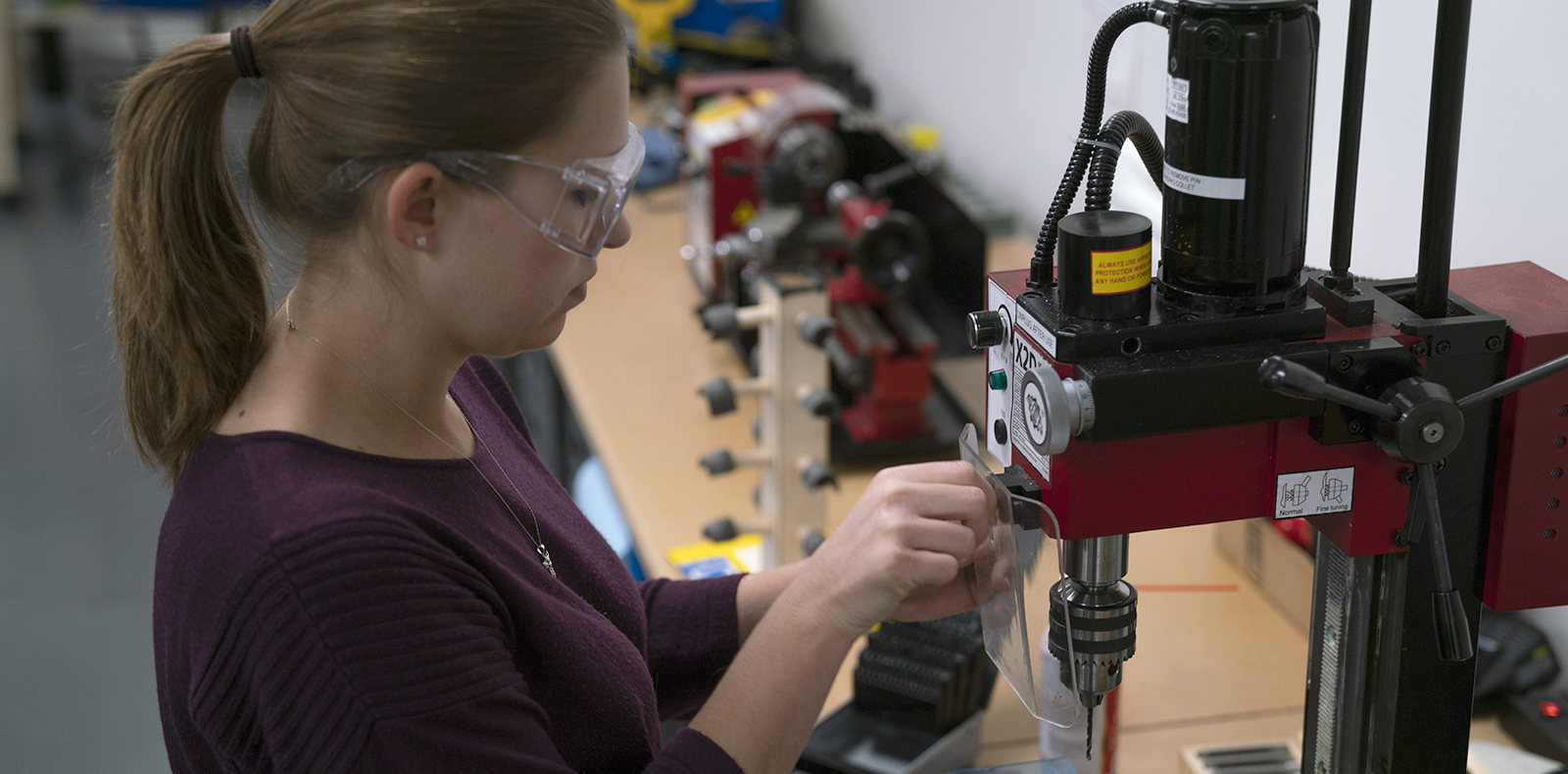 Photograph of a woman concentrated wearing protective eye glasses. Working on a machine in a lab setting.
