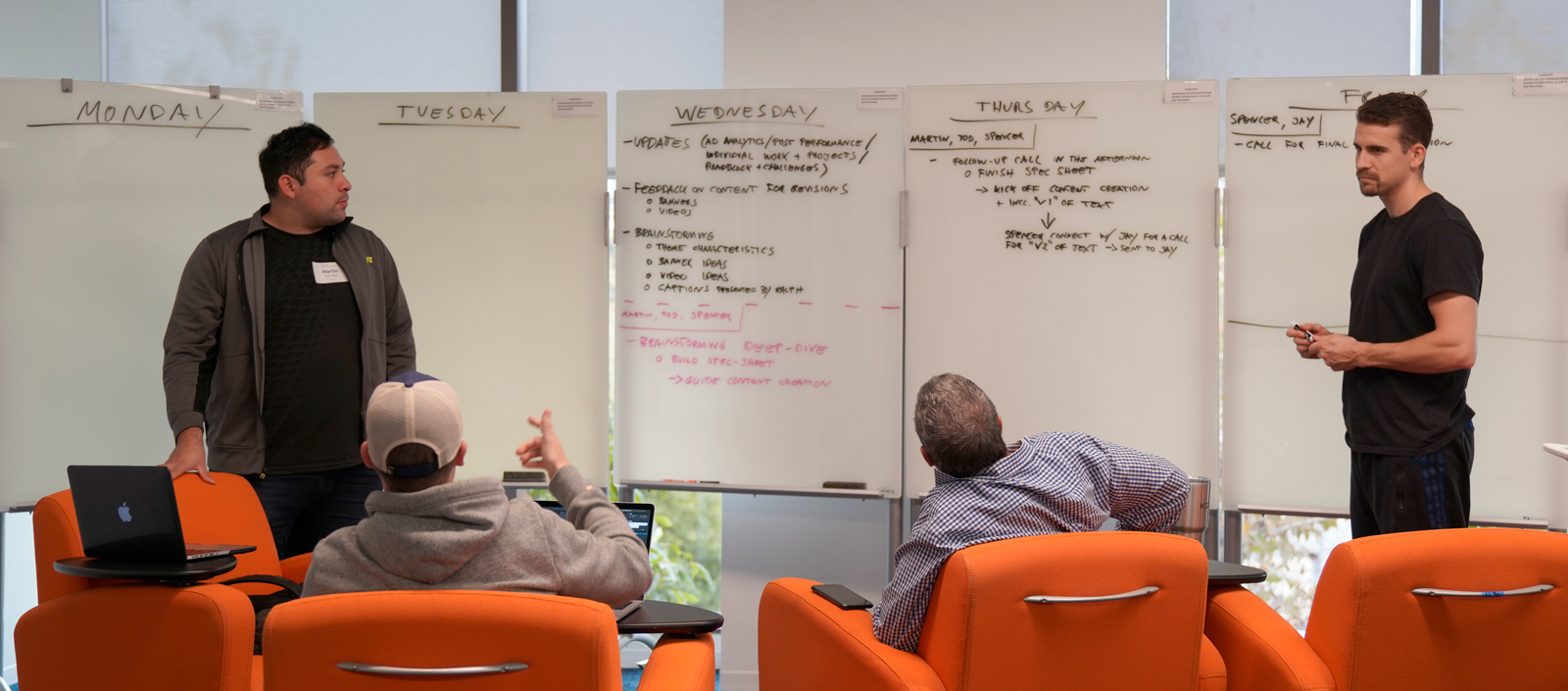 Photograph of a group of men collaborating. Two men standing up, on the right a Hispanic man wearing a jacket. To the right,a Caucasian man standing holding a marker. Two men are sitting down next to one another on orange chairs. All men seem to be collaborating for a weekly structure on the white boards.