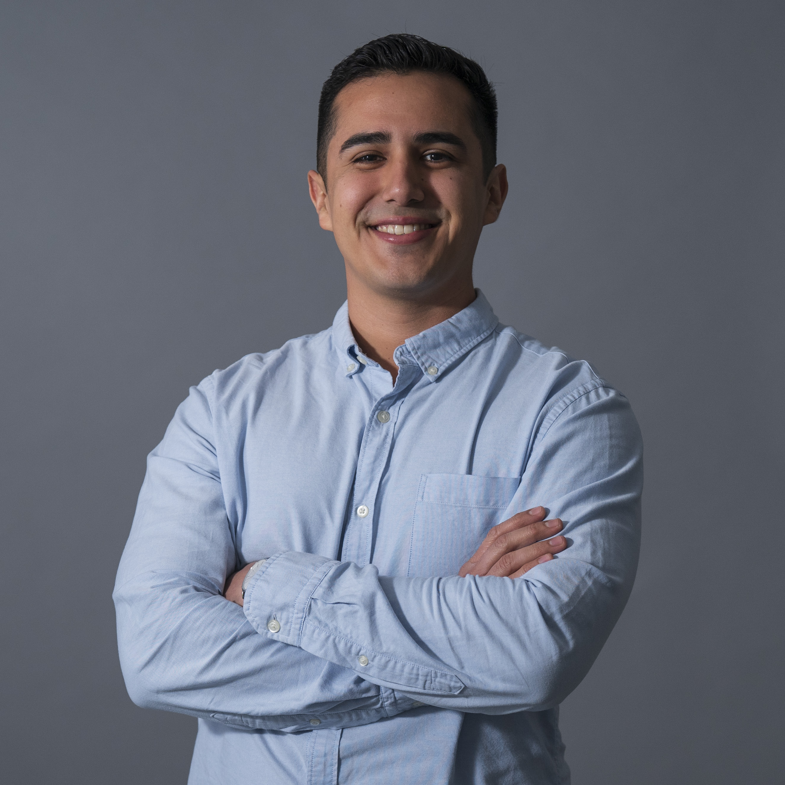 Hispanic young man smiling. Wearing a light blue button up dress shirt. Crossing arms posing for photograph.