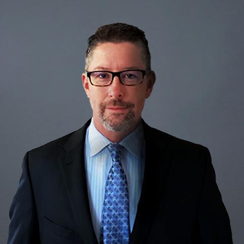 Caucasian Man with glasses, blue dress shirt, blue tie, and a black suit. Studio photoshoot.