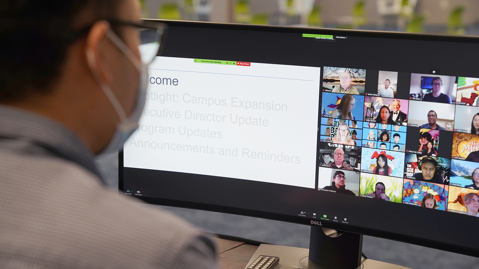 Looking over the shoulder of a person wearing a face mask at a computer monitor screen. On the screen there are participants of a Zoom webinar in a grid on the right side of the screen and Powerpoint presentation on the left side of the screen. The presentation shows an agenda for the meeting.